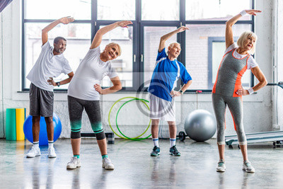 Bild happy multiethnic senior sportspeople synchronous exercising at sports hall