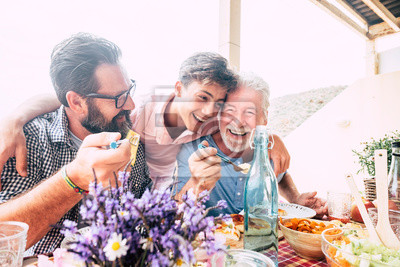 Bild Happy people family concept laugh and have fun together with three different generations ages : grandfather father and young teenager son all together eating at lunch