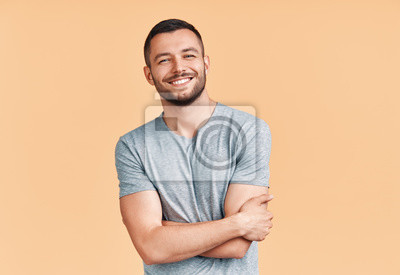 Bild Happy smiling handsome man with crossed arms looking to camera over beige background