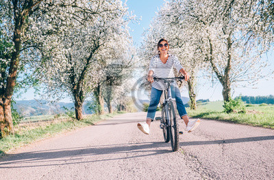 Bild Happy smiling woman rides a bicycle on the country road under the apple blossom trees