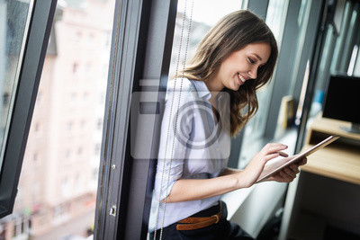 Bild Happy woman manager holding tablet and standing in modern office