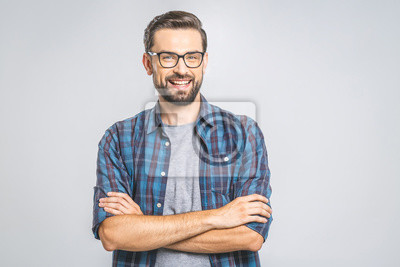 Bild Happy young man. Portrait of handsome young man in casual shirt keeping arms crossed and smiling while standing against grey background