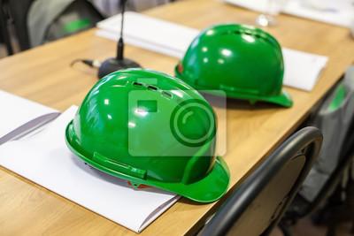 Harte Hüte auf dem Holztisch. Grüne harte Hüte.