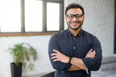 Bild Headshot of skilled hindu male employee standing with arms crossed in modern office, successful confident mixed-race man wearing eyeglasses and smart casual, business portrait of indian entrepreneur