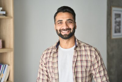 Bild Headshot portrait of attractive confident indian Hispanic man with toothy smile looking at camera at modern living room. Latin businessman posing in casual stylish look at home office.