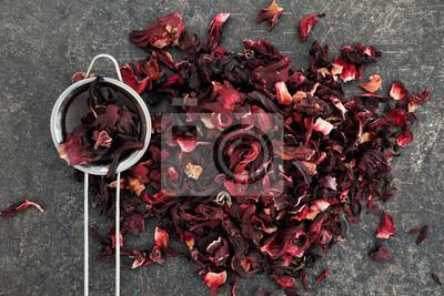 Bild Heap of dry hibiscus tea with sieve on grey background