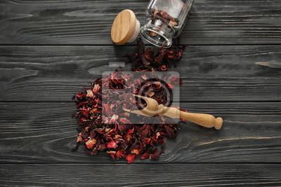 Bild Heap of dry hibiscus tea with wooden scoop on table