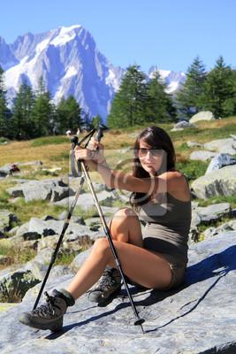 Hiker Mädchen auf einem Stein mit Berg-Walking-Stöcke