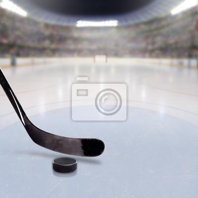 Hockey-Stick und Puck auf Eis der überfüllten Arena