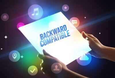 Holding futuristic tablet with BACKWARD COMPATIBLE inscription, new technology concept