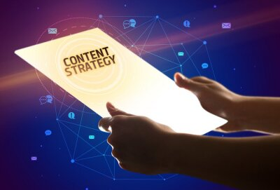 Holding futuristic tablet with CONTENT STRATEGY inscription, social media concept