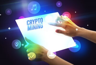 Holding futuristic tablet with CRYPTO MINING inscription, new technology concept