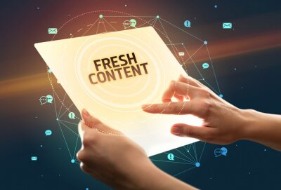 Holding futuristic tablet with FRESH CONTENT inscription, social media concept