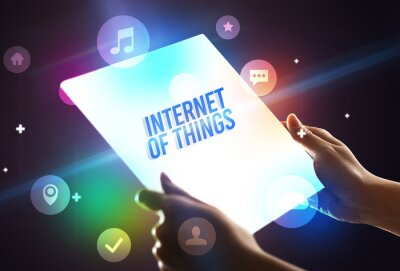 Holding futuristic tablet with INTERNET OF THINGS inscription, new technology concept
