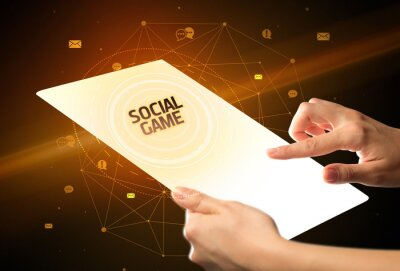 Holding futuristic tablet with SOCIAL GAME inscription, social media concept