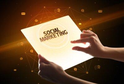 Holding futuristic tablet with SOCIAL MARKETING inscription, social media concept