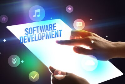 Holding futuristic tablet with SOFTWARE DEVELOPMENT inscription, new technology concept