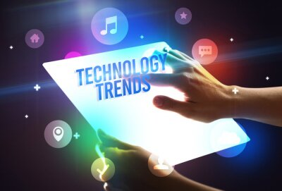 Holding futuristic tablet with TECHNOLOGY TRENDS inscription, new technology concept