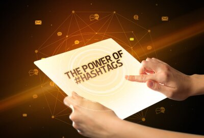 Holding futuristic tablet with THE POWER OF #HASHTAGS inscription, social media concept