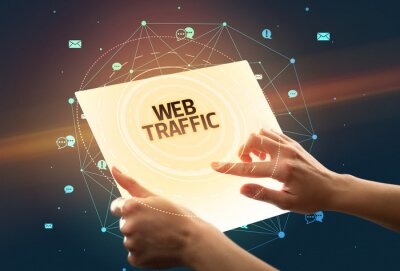 Holding futuristic tablet with WEB TRAFFIC inscription, social media concept