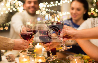 Bild holidays and celebration concept - close up of happy friends having christmas dinner at home, drinking red wine and clinking glasses