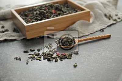 Bild Holzkiste und Löffel mit trockenen grünen Teeblättern auf Tabelle