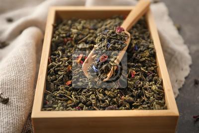 Bild Holzkiste und Schaufel mit trockenen grünen Teeblättern auf Tabelle