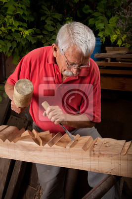 Holzschnitzer arbeiten mit Hammer und Meißel