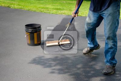 Bild Homeowner spreads blacktop asphalt sealant on driveway