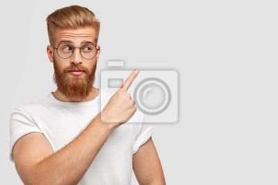 Bild Horizontal shot of attractive Caucasian male has ginger hair and beard, points with fore finger aside, dressed in t shirt in one colour with background, shows blank space for your advertisement