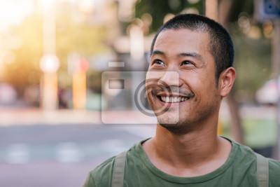Bild Hübscher junger asiatischer Mann, der auf einem Stadtstraßenlächeln steht