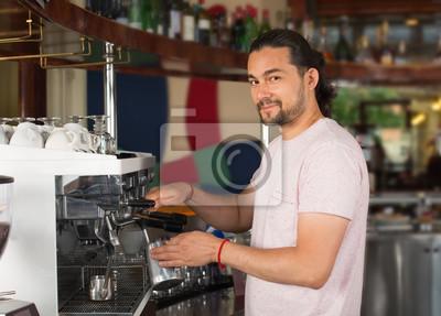Bild Hübscher junger lächelnder männlicher barista, der Kaffeegetränk unter Verwendung der Kaffeemaschine vorbereitet.