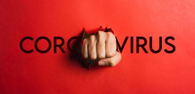 Bild Human hand tearing red paper with the word coronavirus, concept in the fight against coronavirus