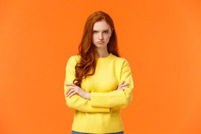 Bild I am mad. Offended sulky cute and timid redhead curly girl, cross arms chest, sulking angry and tensed, frowning stare disappointed someone sad rude words, standing orange background insulted