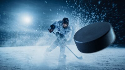 Bild Ice Hockey Rink Arena: Professional Player Shooting the Puck with Hockey Stick. Focus on 3D Flying Puck with Blur Motion Effect. Dramatic Wide Shot, Cinematic Lighting.