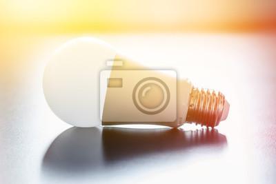 Bild Ideas and innovation: light bulb lying on a desk. Sunlight.