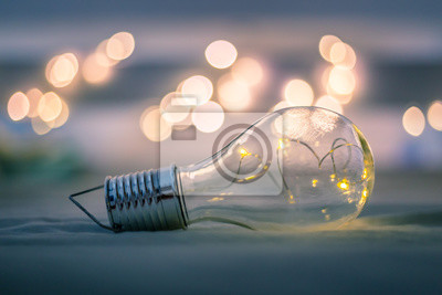 Bild Ideas and innovation: Light bulb with LEDs is lying in the bed. Spot lights in the blurry background.