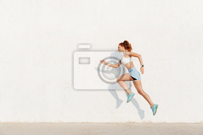 Bild Image of redhead young woman running along white wall while doing workout in morning