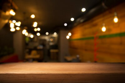 Bild image of wooden table in front of abstract blurred background of restaurant lights