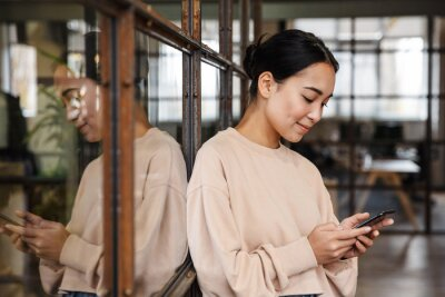 Bild Image of young asian woman holding cellphone while working in office