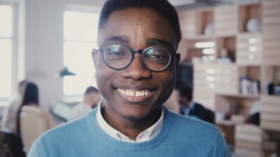Bild Incredible close-up portrait of handsome young African American man in glasses smiling at camera in busy office 4K.
