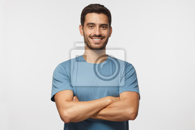Bild Indoor portrait of young european caucasian man isolated on gray background, standing in blue t-shirt with  crossed arms, smiling and  looking straight at camera