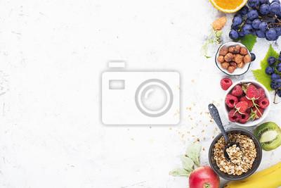 Bild Ingredients for healthy breakfast meals: raspberries, blueberries, nuts, orange, bananas, grapes blue, green, apples, kiwi. Top View.