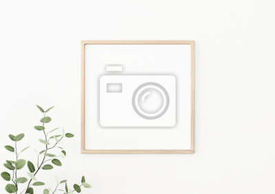 Bild Interior poster mockup with square wooden frame on empty white wall decorated with plant branch with green leaves. 3D rendering, illustration.