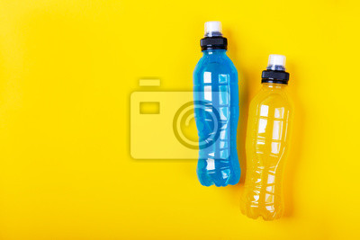 Bild Isotonic energy drink. Bottles with blue and yellow transparent liquid, sport beverage on a colorful background