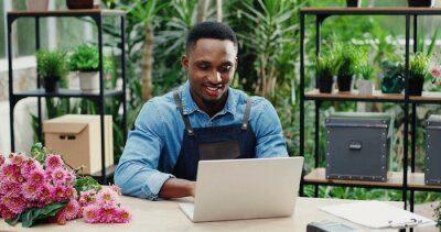 Bild Joyful young man in flower shop sitting at workplace and texting on computer. Cheerful African American male florist worker in floral house tapping and typing on laptop. Floristry concept