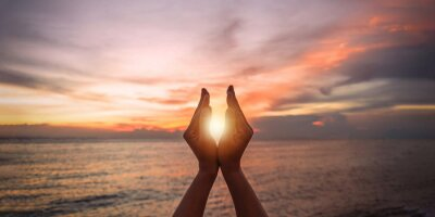 Bild June summer solstice sun concept with silhouette of happy young woman's hands relaxing, meditating and holding sunset against warm golden hour sky on the beach with natural ocean or sea background