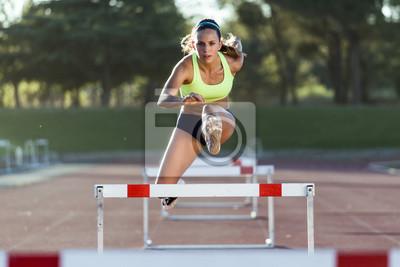 Bild Junge Athleten springen über eine Hürde während des Trainings auf Rennstrecke