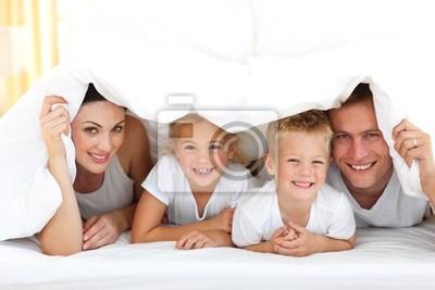 Junge Familie, die zusammen auf einem Bett