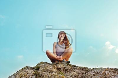 Junge Frau auf dem Gipfel des Berges sitzen